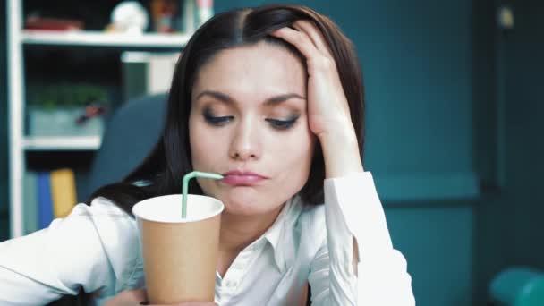 Müde Geschäftsfrau trinkt Kaffee im Büro. Überarbeitungskonzept. Büroangestellte trinkt Kaffee aus einem Strohhalm. Hochwertiges 4k Filmmaterial