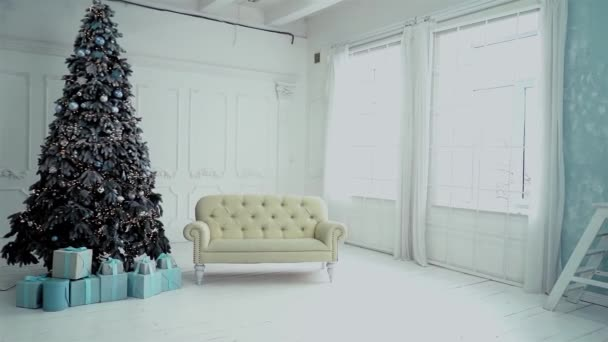 Újévi fotóstúdió áttekintése. Egy karácsonyfa keretén belül, ajándékokkal, egy fehér kanapé mellett. Egy koszorú ég a fán és a golyók lógnak.