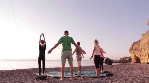 Yoga class group adult women and one man practice yoga and do breathing exercises with instructor on the beach at sunrise.