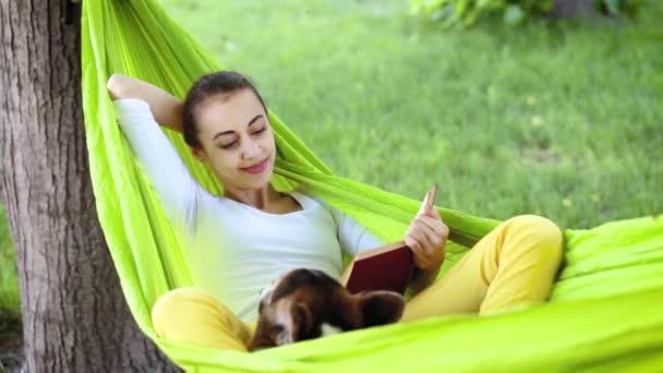 atraktivní mladá žena s roztomilou Velšovou Corgiovou, která leží v zářivě zeleném houpací síti v parku a čte si knihu.