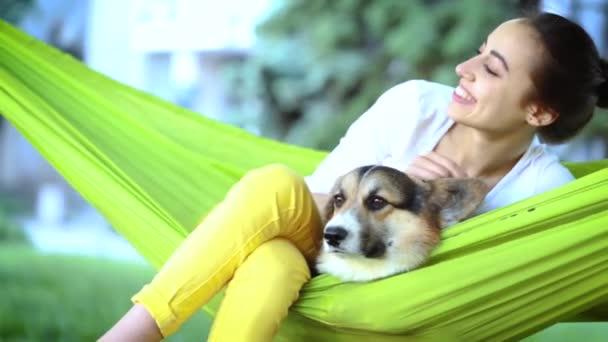 junge hübsche lächelnde Frau mit niedlichen walisischen Corgi Hund in hellgrünen Hängematte im Park liegen