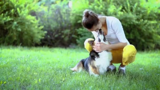 mladá, velmi usměvavá žena s roztomilou Welshcorgiho psem ležící v zářivě zeleném houpací síti v parku
