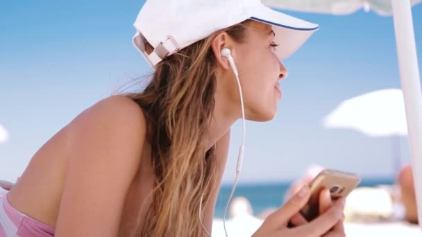 beautiful relaxed slim sexy tanned woman in bikini and white cap with navy blue Union Jack British flag is lying on the beach on a white sand, relaxing and listen music from the phone with small