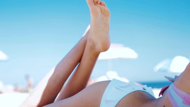 Körperteil einer schönen, athletischen Frau, die sich im Sommer im Bikini am Sandstrand bräunt. Model mit sexy schlankem Körper entspannt im Liegen auf weißem Sand.