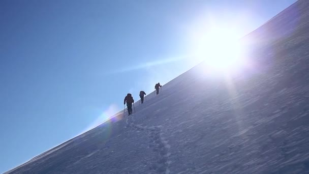 group of climbers moving up by snowy mountain slope. ascent on the Kazbek mount at sunny windy day.