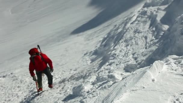 climber moving up by snowy mountain slope. ascent on the Kazbek mount at sunny windy day.