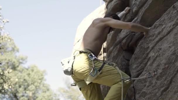 sportos ember rock hegymászó egy sziklán, elérése és megragadta, csatolva Belay kötél.