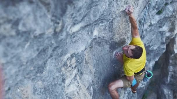 pohled na mužskě horolezec ve žlutém tričku, šplhá po útesu, hledá, sahá a drží. venkovní horolezectví a koncepce aktivního životního stylu