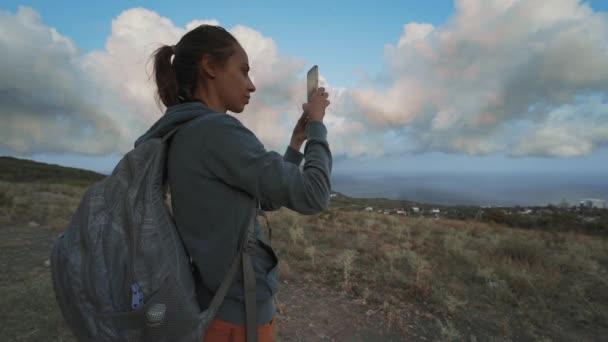 žena turistka vypadá úžasně krásný oblačný západ slunce oblohy a fotografování pomocí mobilního telefonu