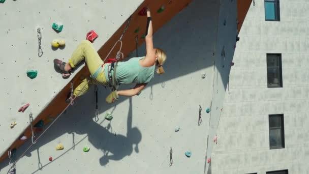 Sportlány mászó mászik a mesterséges sziklafalon kívül mászó tornaterem. Erős nő nehéz lépést tesz