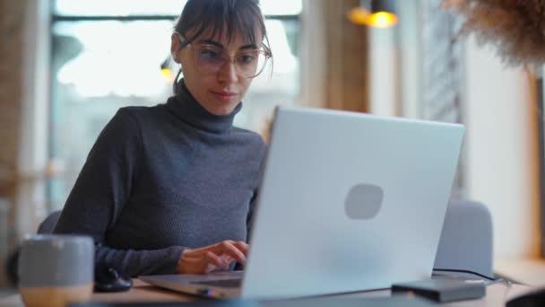 Portré fiatal nő szemüveg segítségével laptop coworking tér vagy kávézó és kávézó