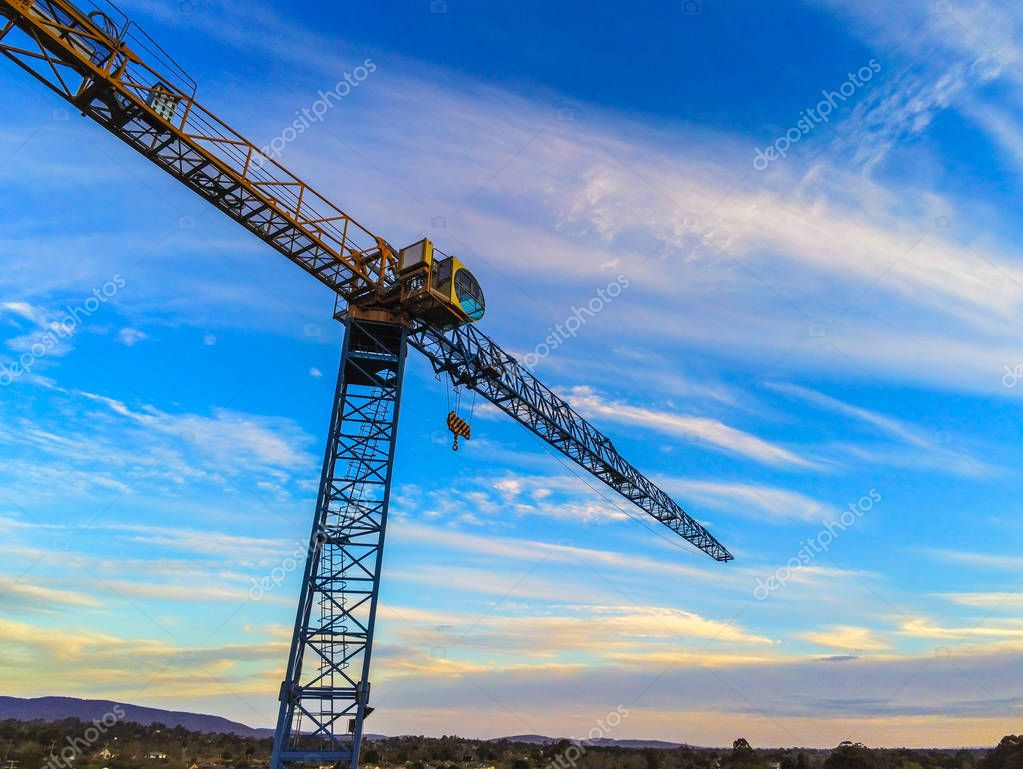 Construction crane tower on cloudy blue sky background.