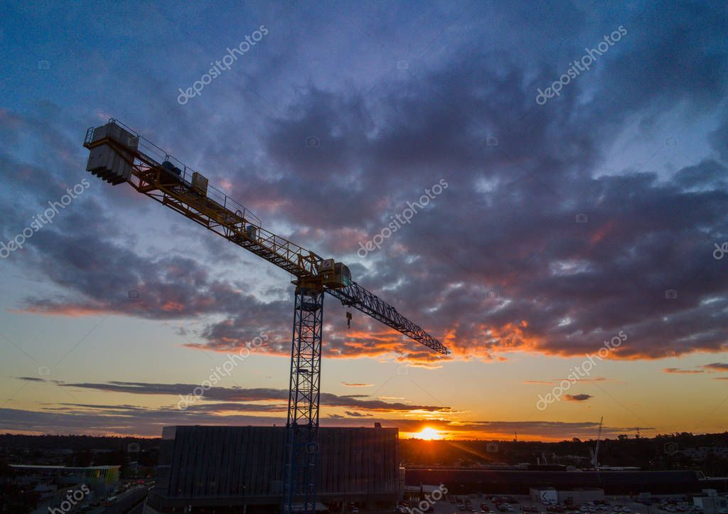 Silhouette crane construction tower with sun setting in the background
