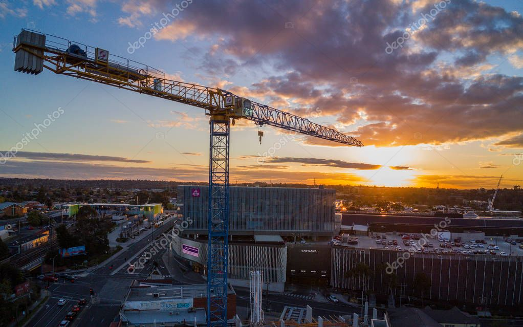 AUSTRALIA, MELBOURNE - SEPTEMBER 17, 2018: Crane construction tower with sun setting in the background
