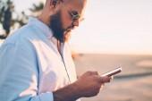 Fotografie Vousatý bokovky chlap drží mobilní telefonní rezervaci na webových stránkách prostřednictvím aplikace, zblízka mladík posílat textové zprávy prostřednictvím smartphonu chatovat s přítelem na městské ulici v sociálních sítích