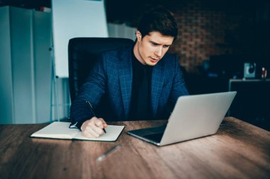 Professional male finance manager checking accountings in app on laptop computer planning budget in notebook,skilled economist reading information from exchange online browsed on netbook in cabinet