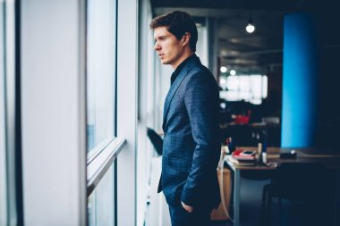 Side view of male corporate director in formal wear thinking about idea for future startup standing near window in office,confident businessman in elegant suit puzzled on solutions for project
