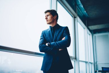 Pensive prosperous businessman in formal outfit looking away in window thinking about future plans and projects,handsome male executive manager puzzled on creative solution for corporation in office