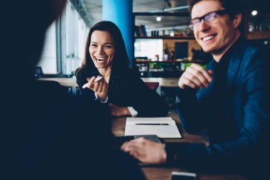 Cheerful formally dressed male and female colleagues laughing on joke during meeting cooperating in friendly atmosphere,carefree business partners enjoying communication about accomplished startup