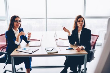 Confident female financial managers in elegant formal wear making creative solutions together, working process of experienced businesswoman planning company budget sitting on meeting table in office
