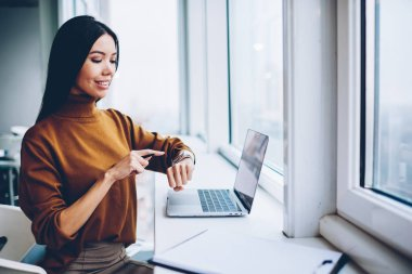 Prosperous businesswoman using and checking notification on touchscreen of wearable computer,professional manager answering sms via smart watch synchronizing multimedia with laptop computer