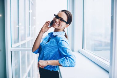 Portrait of cheerful businesswoman in formal wear excited with good news about startup celebrating victory during phone call, emotional prosperous female manger looking at camera talking on cellular