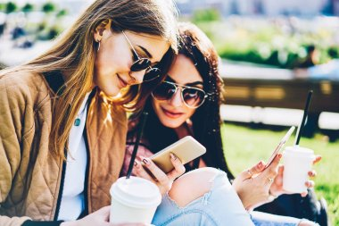 Stylish female bloggers in sunglasses publishing new posts on own websites and reading comments under it on modern smartphone devices sitting outdoors on green grass with tasty coffee in hands