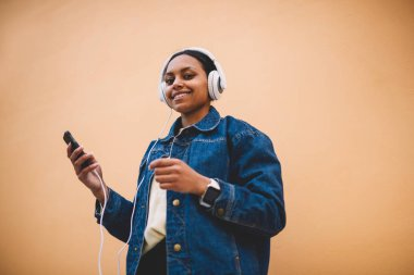 Happy afro american girl in jeans jacket and headphones enjoying favorite songs while standing on background with copy space. Smiling female black model listening music via application on cellular