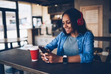Cheerful afro american hipster girl listening music in modern red headphones communicating online with friend.Happy dark skinned student enjoying coffee break blogging in networks via cellular
