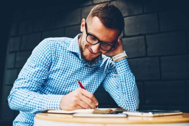 Positive hipster guy in spectacles concentrated on writing ideas for coursework project in college campus,skilled male architect drawing graphic in sketchbook satisfied with creative working process