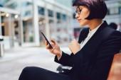 Boční pohled podnikatelka ve stylovém oblečení a brýle na lavičce odesílání zpráv na smartphone. Jistý majitel firmy pomocí mobilní aplikace pro internetové bankovnictví na mobilní zařízení