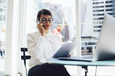 Serious businesswoman in elegant wear talking on phone doing remote job in cafe with laptop.Female entrepreneur in formal clothes discussing information from documents communicating on cellular