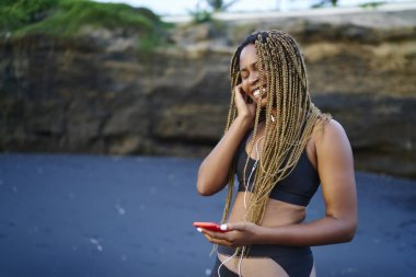 Cheerful afro american young woman happy from audio songs listening in earphones standing on beach during morning run.Dark skinned female dressed in sportive wear enjoying music player on smartphone