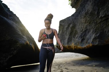 Positive afro american female jogger dressed in active clothes choosing music in player downloaded on smarthone for morning training on seashore.Cheerful young woman in tracksuit and earphones