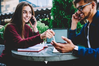 Smiling male and female colleagues satisfied with productive job making phone calls for finding out information, skilled creative employees concentrated on project having mobile conversations