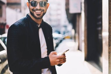 """Картина, постер, плакат, фотообои """"обрезанное изображение жизнерадостного хипстера, смотрящего на камеру в чате с другом в сети через смартфон, стоящий на городской улице, портрет улыбающегося мужчины, отправляющего мультимедийные сообщения через сотовый телефон архитектур природа"""", артикул 207039216"""