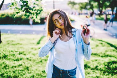 Young woman in eyewear dancing while listening favorite music via earphones and mobile resting in park, positive hipster girl relaxing with songs enjoying sound and playlist moving in rhythm