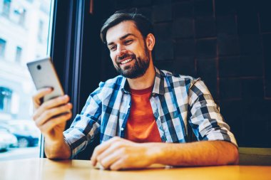 Successful bearded young man messaging in online chat on modern smartphone via 4G internet sitting in coworking space.Positive hipster blogger reading notification with good news on cellular device
