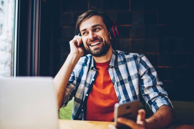 Positive bearded blogger enjoying electronic music in headphones connected via bluetooth to telephone.Cheerful casual dressed young man listening audio songs from playlist downloaded on smartphone