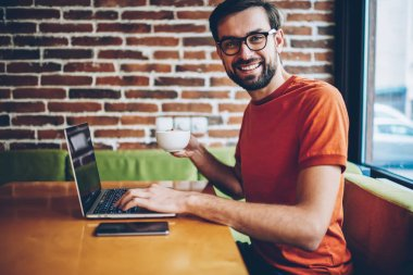 Portrait of successful bearded young man freelancer smiling at camera while holding cup of coffee in hand and updating software on modern laptop computer connected to 4G internet sitting in cafe
