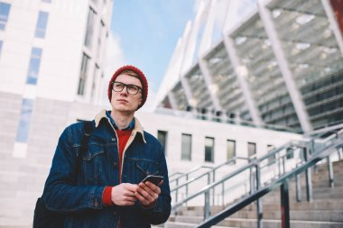 Thoughtful hipster student in eyewear walking on street with smartphone in hands to send sms message.Pondering young man checking mail with notifications in social networks on mobile phone