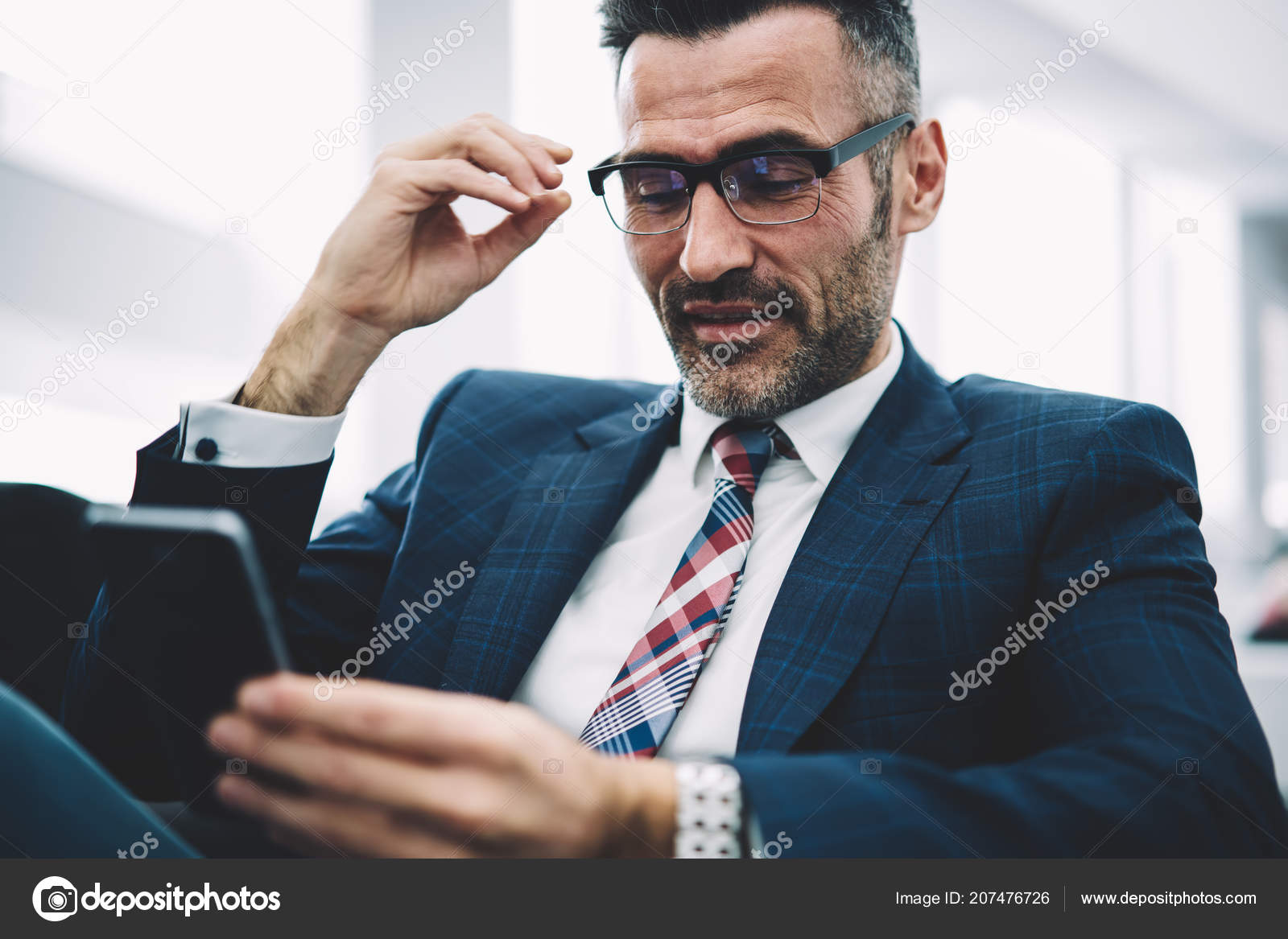 d97330c215b8 Cheerful mature entrepreneur reading funny notification on smartphone  device sitting in office.Successful proud ceo in formal wear chatting  online on ...