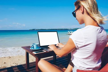 Young woman millennial keyboarding on netbook with mock up screen communicating in online chat sitting near ocean, businesswoman working distantly on vacation in tropical environment enjoying natur