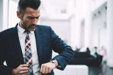 Confident mature entrepreneur dressed in formal wear checking time on watch standing in office of financial company.Serious busy corporate director middle aged.Successful businessman in suit
