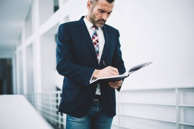 Pensive mature proud ceo dressed in formal wear writing down records in notepad developing business strategy.Concentrated businessman 50 years old signing financial documents of corporate company