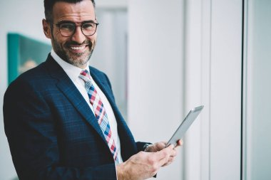 Half length portrait of successful mature businessman in formal wear smiling at camera while making money transaction online on touch pad via 4G internet connection.Prosperous proud ceo with tablet