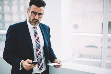 Half length portrait of confident mature proud ceo in suit looking at camera while dialing number on smartphone.Successful serious businessman with documents checking mail on cellular near copy space