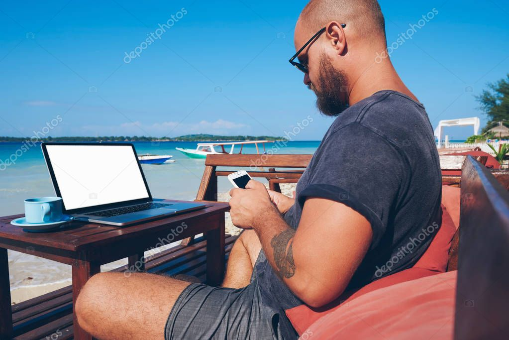 Young man using modern technology and 4G internet working remotely on ocean beach in summer, millennial male blogger checking notification on smartphone update his web page content on journe