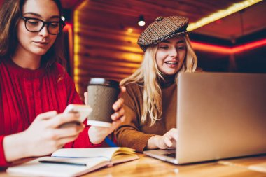 Young hipster girls spending coffee break together but addicted to modern technology ignoring live communication, female students enjoying free wifi connection in cafe for networking on device