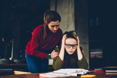 Sympathetic young woman supporting despaired student wich don't understand confused studying information during exam preparation in coworking.Exhausted hipster girl learning material from textbook